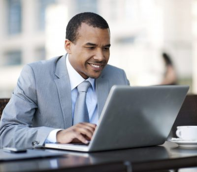 A smiling young man using his laptop.  [url=http://www.istockphoto.com/search/lightbox/9786622][img]http://img543.imageshack.us/img543/9562/business.jpg[/img][/url]